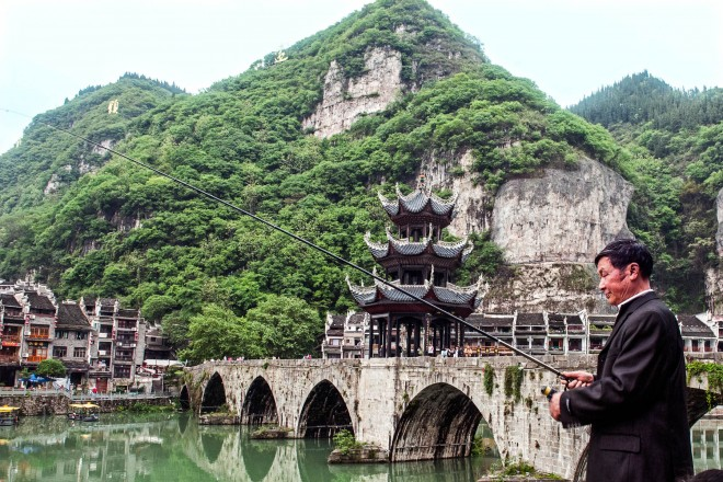 An elegant fisherman fishing on Wuyang River in Zhenyuan, Guizhou province, China