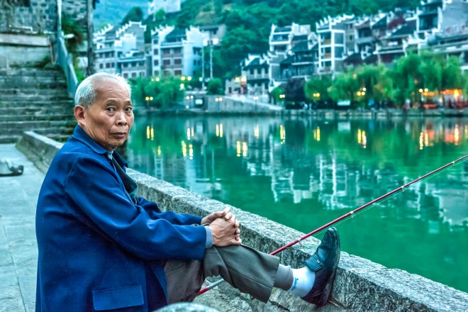 An old man fishing over the Wuyang River among the houses of Zhenyuan, in Guizhou province, China