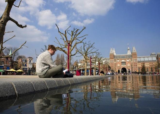 Rijksmuseum gezien vanaf richting concertgebouw. . Foto is vanuit de vijver op het museumplein genomen. Links voor in beeld zit een jongeman in een beige gebreide trui aan de vijver te lezen. Mooi blauwe, gedeeltelijk bewolkte lucht
