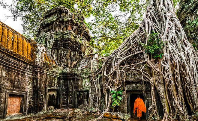 Un monaco tra le rovine del tempio di Ta Prohm in Cambogia