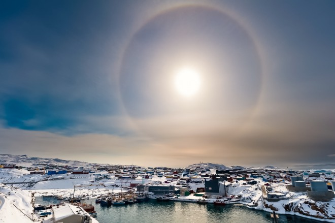A solar halo over the town of Ilulissat, an optical phenomenon caused by the light interacting with ice crystals in the atmosphere.