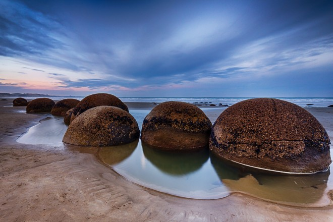 """Koekohe Beach, Nuova Zelanda - Una distesa di sabbia con sfere di roccia che affiorano dall'acqua. Sembrano tante """"uova di drago"""", ma in realtà si tratta di scogli di roccia sedimentaria levigati dall'acqua dal continuo infrangersi delle onde sulla loro superficie."""